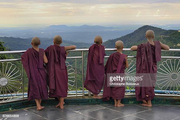 Buddhist novices watching sunrise near the Golden Rock