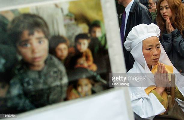 Buddhist nun chants next to a banner portraying Afghan children October 2 2001 during a vigil for peace opposite the British Prime Minister's...