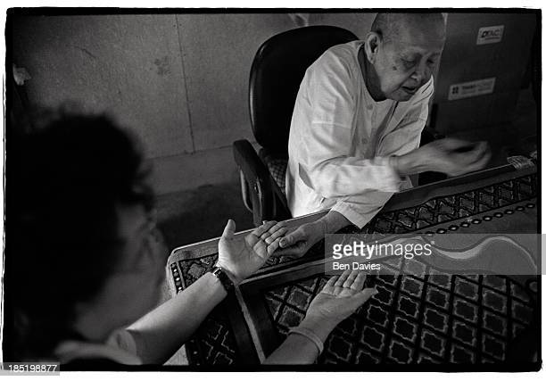 Buddhist nun or maechee reads a devotee's palm at the Nang Nak Shrine in Bangkok the capital of Thailand Many Thai people are animist They believe in...