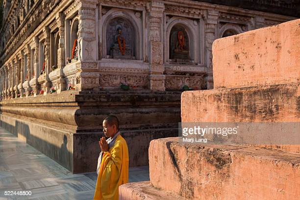 BODHGAYA BIHAR INDIA BODHGAYA BIHAR INDIA Buddhist nun walking and praying at the Mahabodhi Mahavihara temple in Bodh Gaya Bihar India The Mahabodhi...