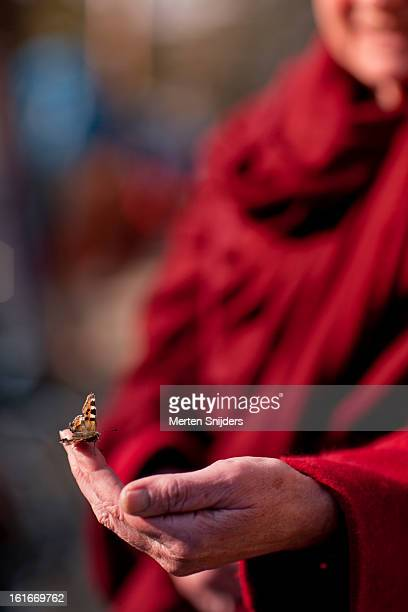 Buddhist nun with butterfly on her hand