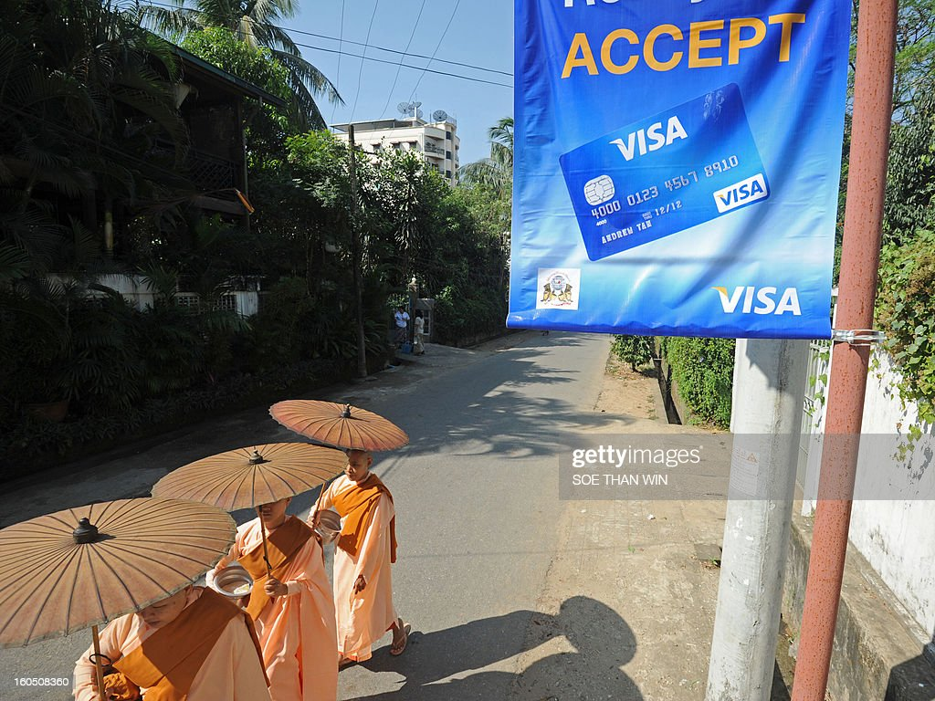 Buddhist nuns on their way for alm pass by a Visa advertistment in Yangon on February 2, 2013. US credit card giant Visa launched electronic payments in Myanmar, marking the long-awaited debut of plastic in a country that until now has had a cash economy. AFP PHOTO/Soe Than WIN