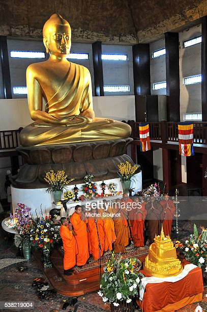 Buddhist Pagoda in Vincennes. Presentation of the Buddha's relics in Paris. Monks praying in front of the big statue of Buddha.
