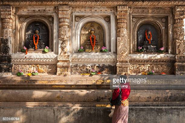 BODHGAYA BIHAR INDIA BODHGAYA BIHAR INDIA Buddhist pilgrim offering flowers by the Buddha carvings of the Mahabodhi Mahavihara temple in Bodhgaya...