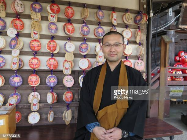 Buddhist priest Isshin Hirose stands in front of wooden votive plaques called 'ema' some of them having white stickers to hide information at...