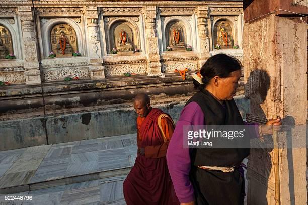 BODHGAYA BIHAR INDIA BODHGAYA BIHAR INDIA Buddhist Tibetan pilgrim and monk walking and praying at the Mahabodhi Mahavihara temple in Bodh Gaya Bihar...