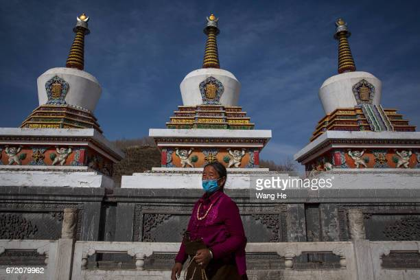 A buddhist worshippers walk around the in the courtyard of the Kumbum Monastery on April 23 2017 in Xining Qinghai Province Kumbum was founded in...