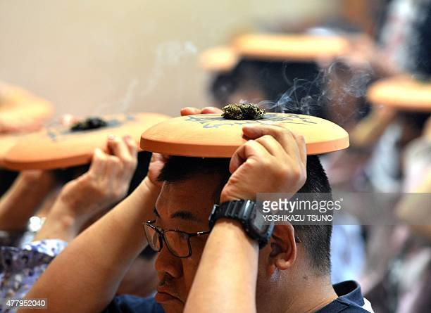 Buddhists burn moxa atop unglazed plates on their heads as they chant for good health in a traditional summer ritual at Tokyo's Chokokuji temple on...