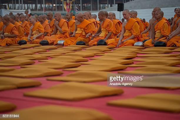 Buddist monks sit next to alms bowls as over 100000 buddhist monks and novices gather at Wat Dhammakaya Temple before the 'AlmsOffering Ceremony' to...