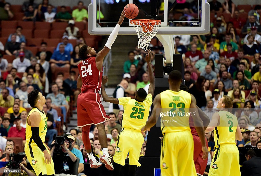 Buddy Hield of the Oklahoma Sooners dunks over Chris Boucher of the Oregon Ducks in the first half in the NCAA Men's Basketball Tournament West...