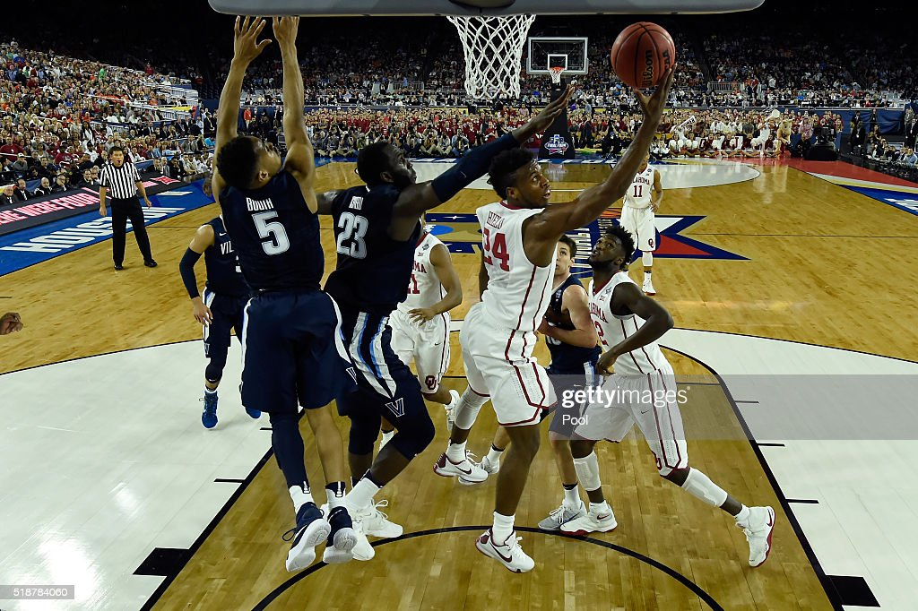 Buddy Hield of the Oklahoma Sooners shoots the ball against Daniel Ochefu of the Villanova Wildcats and Phil Booth in the first half during the NCAA...