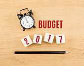 Budget 2017 year on wood cube with pencil and clock top view on wood table,New year business concept.