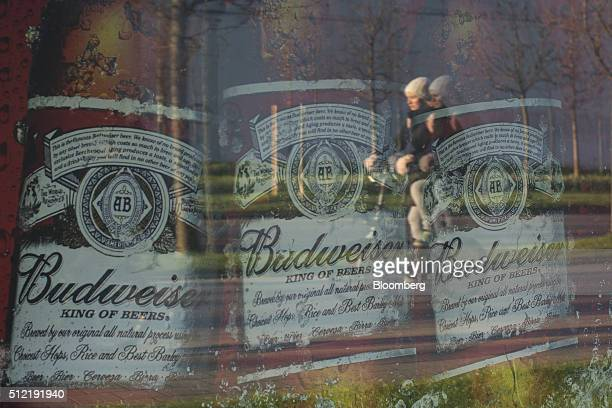 A Budweiser beer advertisement sits in the windows of the AnheuserBusch InBev NV headquarters in Leuven Belgium on Thursday Feb 25 2016 AB InBev's...