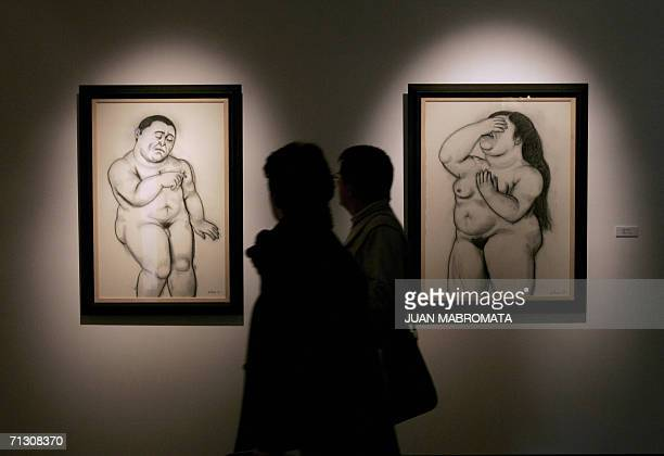 A couple of visitors watch 27 June 2006 drawings by Colombian artist Fernando Botero 'Terror' and 'Woman Crying' part of the exhibit 'Colombia's Pain...