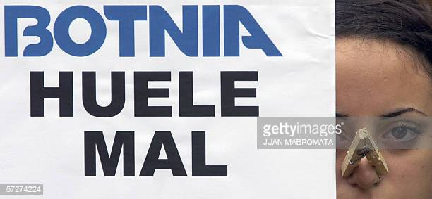 A Greenpeace supporter using a clothes pin on her nose shows a poster that reads 'Botnia Smells Bad' during a protest at Plaza de Mayo square in...