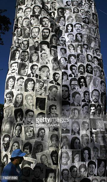 A man walks in front of a huge banner with pictures of some of the disappeared in the last dictatorship 30 April 2007 in Plaza de Mayo in Buenos...