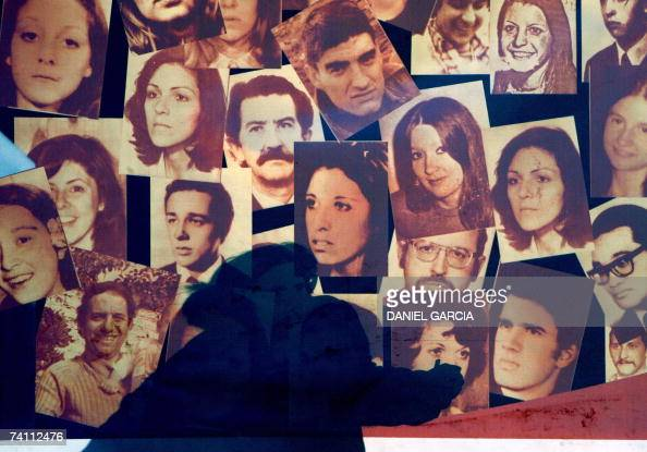 A woman touches 30 April 2007 the picture of a person disappeared during the military dictatorship in Argentina on a translucent banner hung in Plaza...