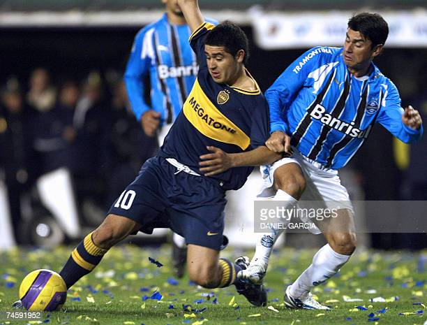 Defender Patricio of Gremio pulls the shirt of midfielder Roman Riquelme of Boca Juniors during the first leg final football match of the Copa...