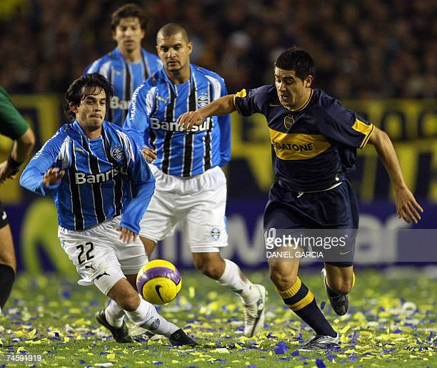 Midfielder Roman Riquelme of Boca Juniors vies for the ball with Diego Gavilan of Gremio during the first leg final football match of the Copa...