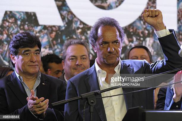 Buenos Aires province governor and presidential candidate for the Frente Para la Victoria Daniel Scioli raises his fist next to his running mate...