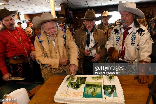 Buffalo Bill impersonators Buzz Baker second from left cuts the anniversary cake with help from other impersonators Jason Baker left Stanley Beug...