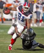 Buffalo Bills running back Willis McGahee tries to break free from grasp of Oakland Raiders rookie cornerback Fabian Washington during 3817 loss at...