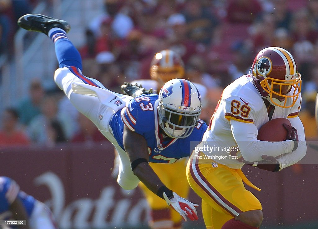Buffalo Bills safety Aaron Williams (23) goes airborne trying to tackle Washington Redskins wide receiver Santana Moss (89) after a first down catch in the first quarter during a preseason game between the Buffalo Bills and the Washington Redskins at FedEx Field on August 24, 2013 in Landover, Md.