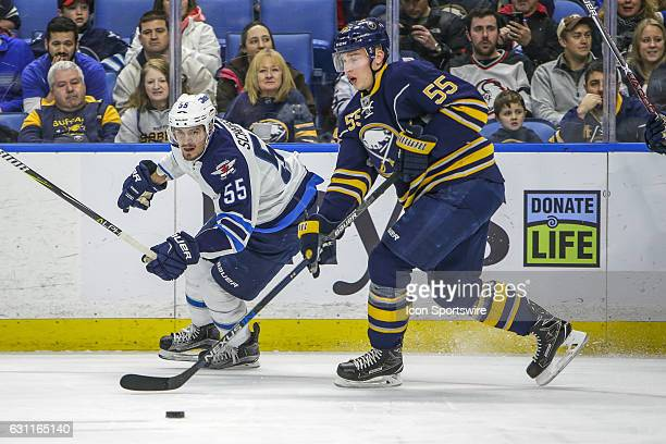 Buffalo Sabres Defenseman Rasmus Ristolainen and Winnipeg Jets Center Mark Scheifele fight for the puck during the New Winnipeg Jets and Buffalo...