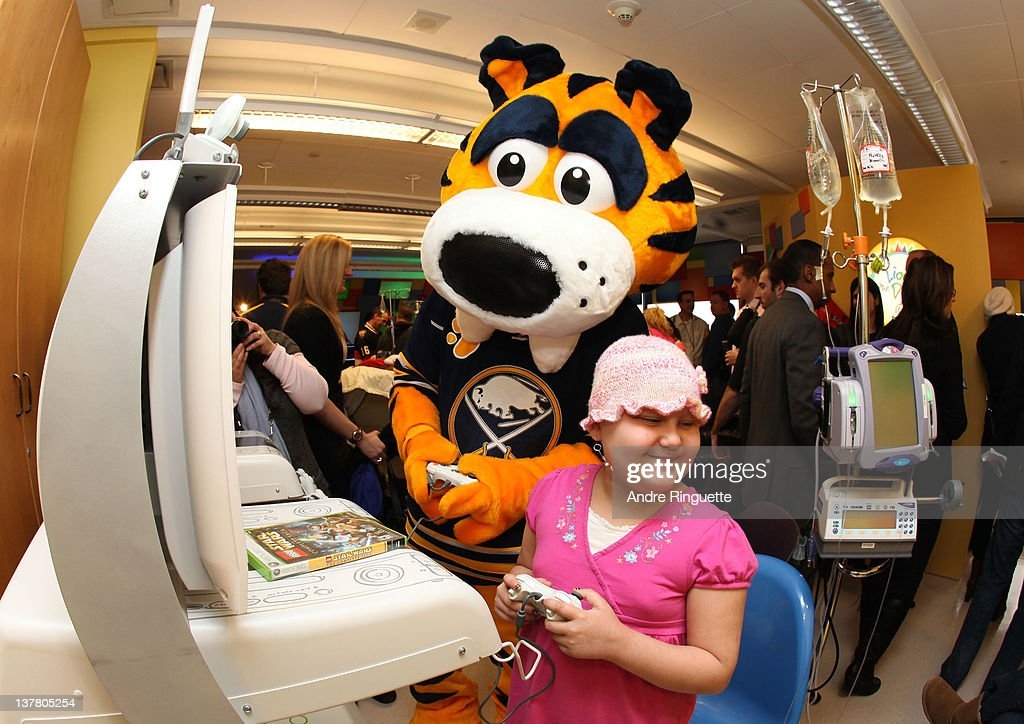 Buffalo Sabres mascot Sabretooth and a young patient play a video game at the unveiling of the NHL All-Star Legacy Playroom at Children's Hospital of Eastern Ontario on January 27, 2012 in Ottawa, Canada.