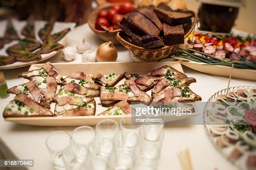 Buffet table of reception with fish burgers, cold snacks : Stock Photo