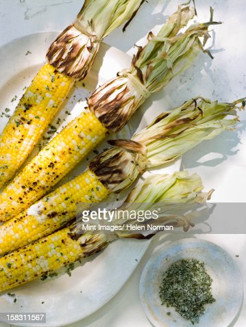 A buffet table set up in a garden for al al fresco meal. Sweetcorn, corn on the cob. : Stock Photo