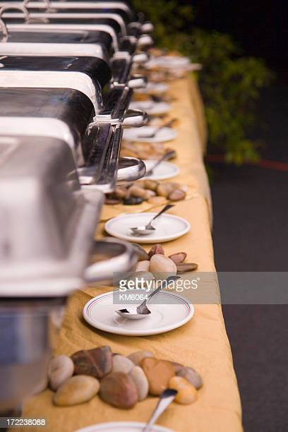 Buffet table setup with plates and spoons