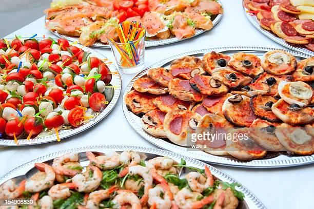 Somptueux buffet avec des tomates, des pizzas, du saumon et des crevettes