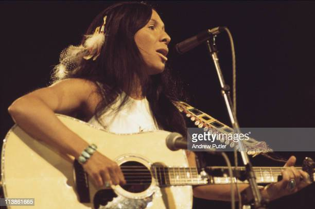 Buffy SainteMarie Cree singersongwriter playing guitar while singing into a microphone during a live concert performance at the International...