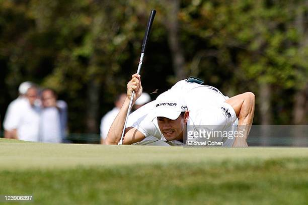 A bug hovers over the head of Camilo Villegas of Colombia as he reads the green prior to s putt attempt on the second hole during the final round of...