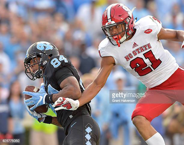 Bug Howard of the North Carolina Tar Heels makes a touchdown catch against Nick McCloud of the North Carolina State Wolfpack during their game at...