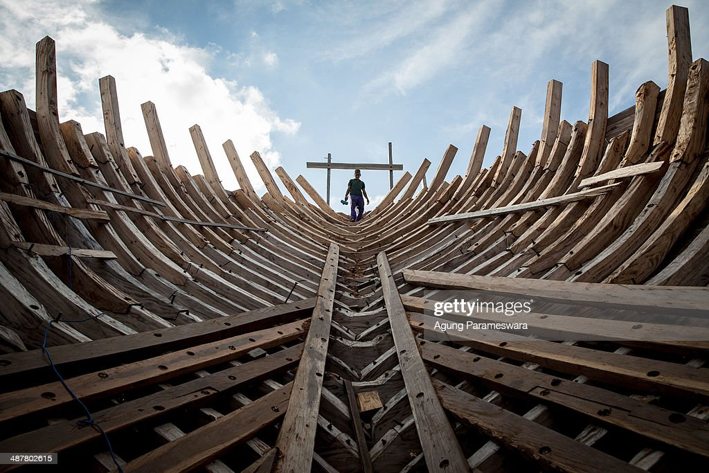 A Buginese man holds a hammer as he starting to work to install a wooden block in the hull of phinisi at Tanjung Bira Beach on May 2, 2014 in Bulukumba, South Sulawesi, Indonesia. Phinisi, a masterpiece of traditional Bugis-Makassar design, is a traditional wooden two-masted sailing ship, well-known as traditional sea transportation amongst the buginese people for many centuries. According to the ancient I La Galigo manuscript, phinisi has already existed since around the 14th century. The scooners are largely built using the design and construction techniques handed down from generation to generation over hundreds of years.