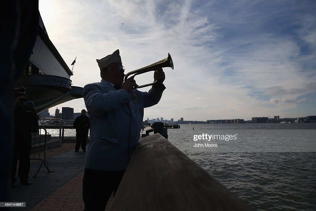 A bugler plays Taps at a ceremony marking the 72nd anniversary of the attack on Pearl Harbor, Hawaii on December 7, 2013 in New York City. Four Pearl Harbor survivors from the New York area gathered with former crew members of the USS Intrepid to mark the Japanese surprise attack on December 7, 1941 which killed 2,402 Americans and brought the United States into WWII.