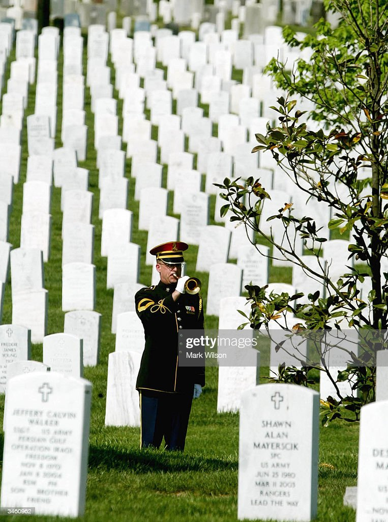 A bugler plays taps during a funeral for US Army Sgt. Yihiyh Chen at Arlington National Cemetery, April 23, 2004 in Arlington, Virginia. Chen was killed on April 4th in Baghdad, Iraq when his unit was attacked with rocket propelled grenades and small arms fire.