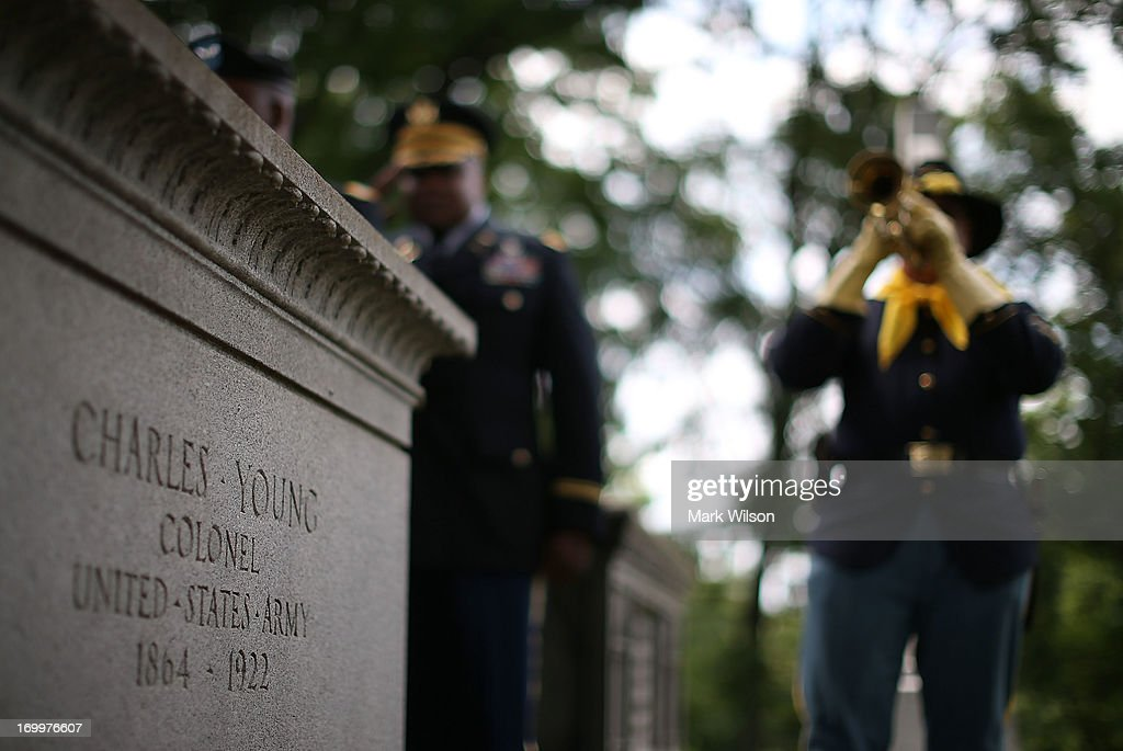 A bugler plays Taps during a wreath laying ceremony at the gravesite of Buffalo Soldier Col. Charles Young, at Arlington Cemetery, June 5, 2013 in Arlington, Virginia. The event was hosted by the National Coalition of Black Veterans and the Omega Psi Phi Fraternity to celebrate the 90th anniversary of 'Buffalo Soldier' and military leader Col. Charles Young's internment in Arlington Cemetery.