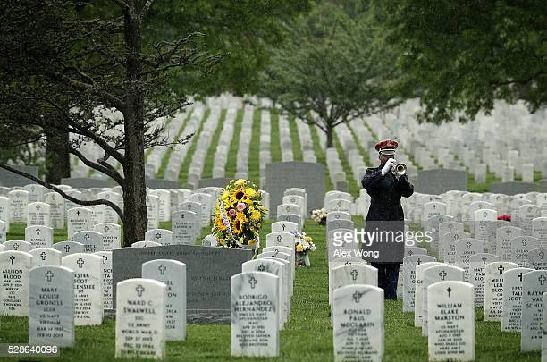 A bugler plays 'Taps' during the funeral of Army Corporal David J Wishon at Arlington National Cemetery May 6 2016 in Arlington Virginia Corporal...