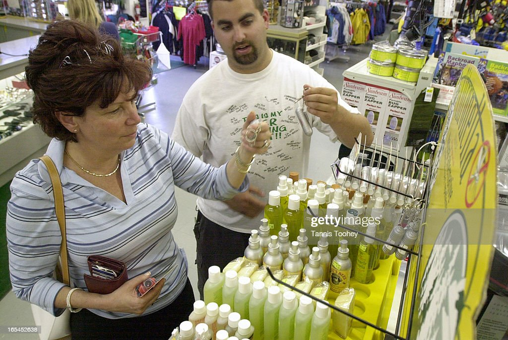 June 11, 2003-Mathew Dimitry from Tent City Outfitters in Concord aids shopper Ann Laski on which bug spray will protect her family the best.(low and high concentrations of DEET, citronella based sprays, etc.) as concerns about West Nile virus grows, Wednesday June 11, 2003.