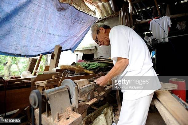 Bui Van Vuoc makes a part of a traditional music instrument at his workshop in Vinh Bao on September 19 2015 in Hai Phong Vietnam 81yearsold Bui Van...