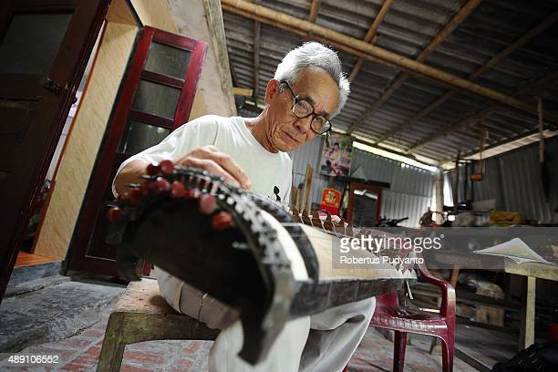 Bui Van Vuoc makes final inspection on a dan thap luc instrument at his workshop in Vinh Bao on September 19 2015 in Hai Phong Vietnam 81yearsold Bui...