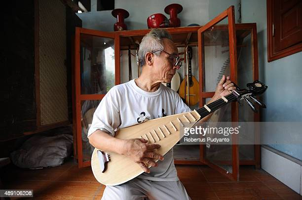 Bui Van Vuoc makes final inspection on a dan ty ba instrument at his gallery in Vinh Bao on September 19 2015 in Hai Phong Vietnam 81yearsold Bui Van...