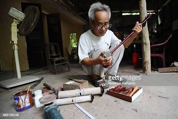Bui Van Vuoc sets up parts of a dan nhi instrument at his workshop in Vinh Bao on September 19 2015 in Hai Phong Vietnam 81yearsold Bui Van Vuoc of...