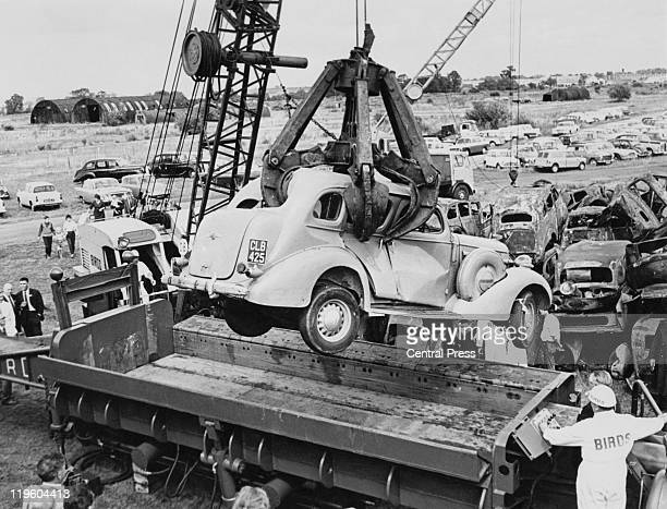 A buick car being lowered in to a mobile carcrusher at Birds' depot at Long Marston Warwickshire 1963