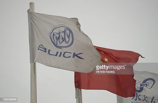 A Buick flag flies beside a Chinese flag at a General Motors dealership in Shanghai on December 6 2011 The US auto giant said its sales in China...