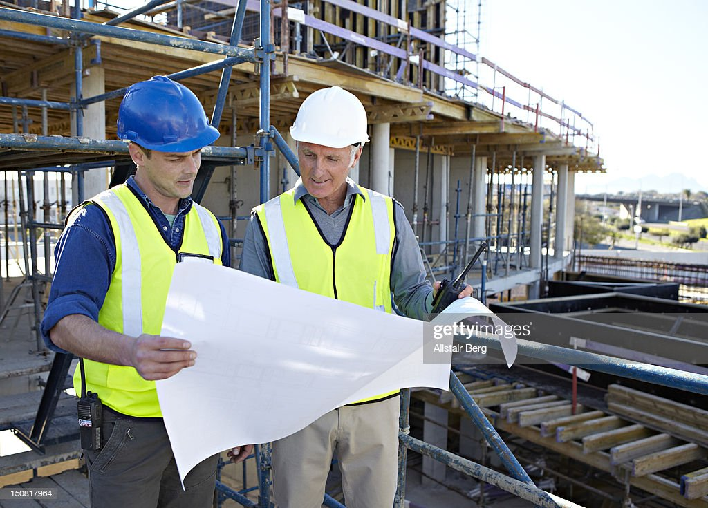 Builder and architect on building site : Stock Photo