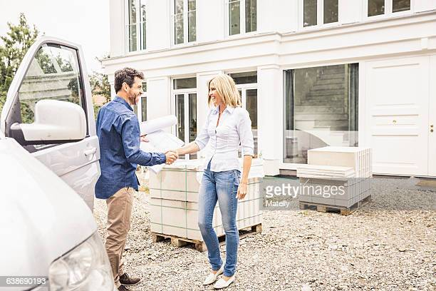Builder arriving in van, shaking hands with homeowner smiling